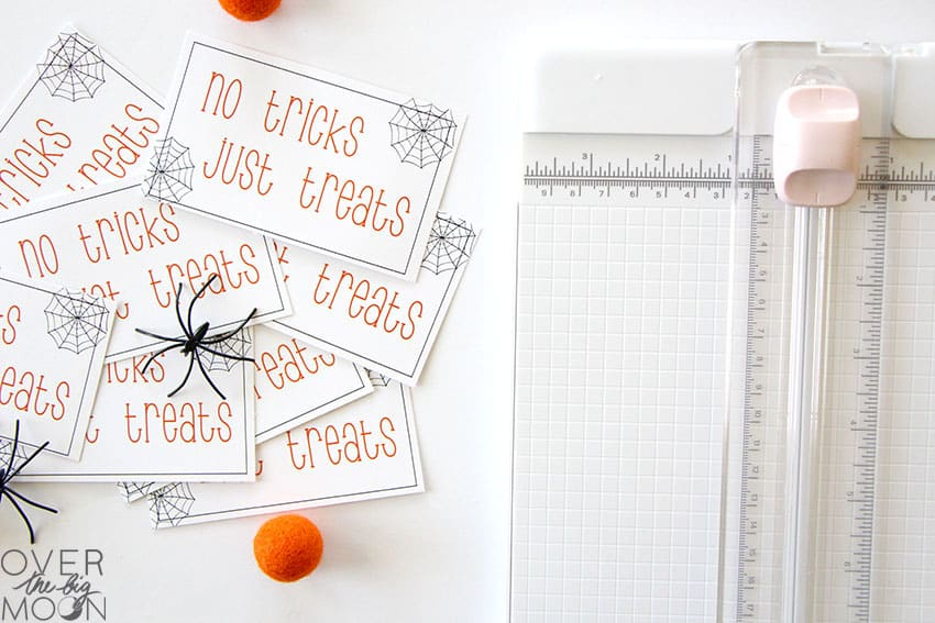 A pile of printed gift tags that say No Tricks, Just Treats on them, next to a paper cutter.