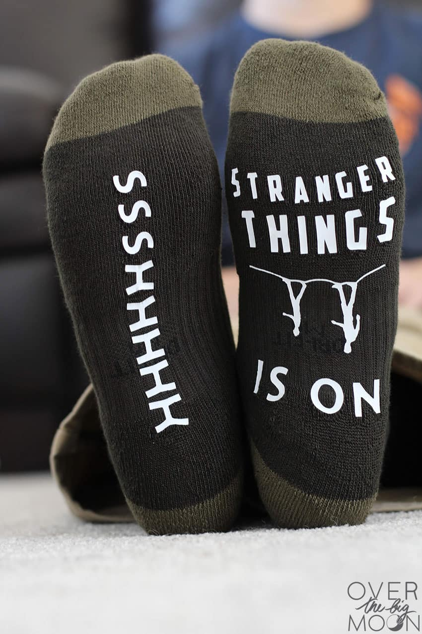 A pair of feet - one that says ssshhhhh on it and the other says Stranger Things is on.
