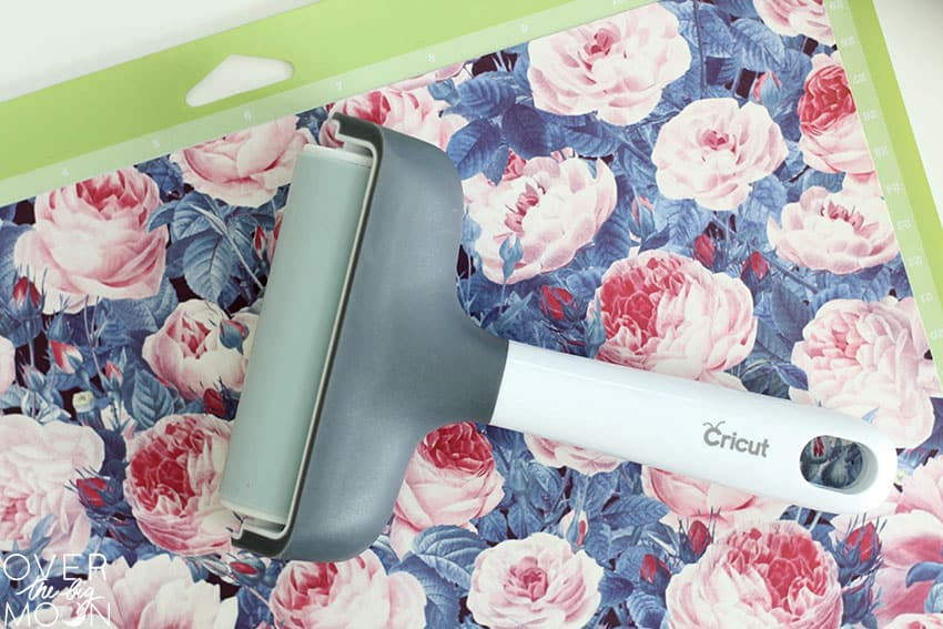 Floral Infusible Ink applied to a green Cricut mat, with a brayer laying on top of it.