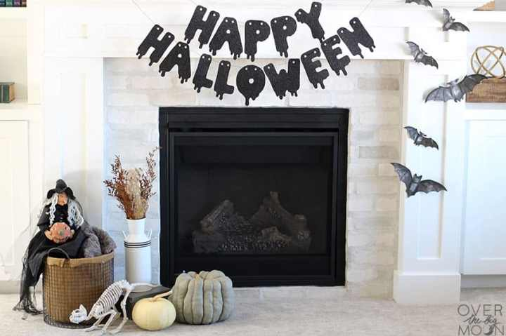 Fireplace mantel decorated for Halloween - with Happy Halloween banner, cardstock bats and pumpkins!
