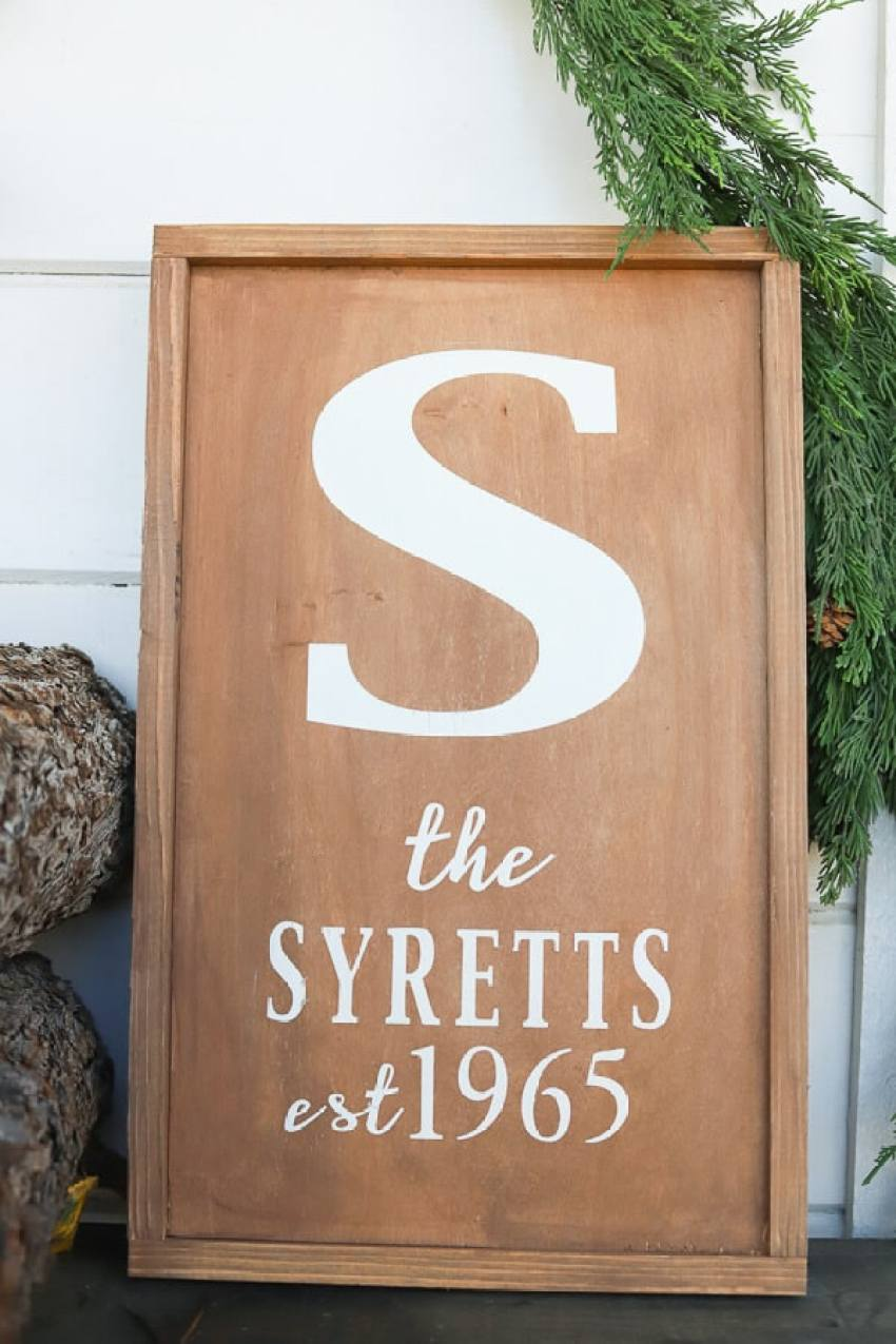 A wooden sign with Vinyl that says a name and the year the year of marriage on it.