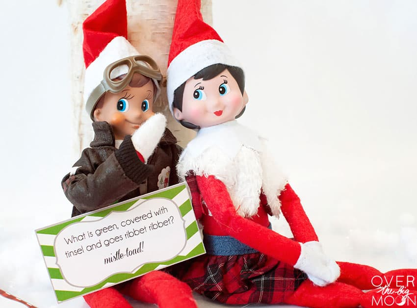 A boy elf and girl elf hanging out and laughing over the joke card.