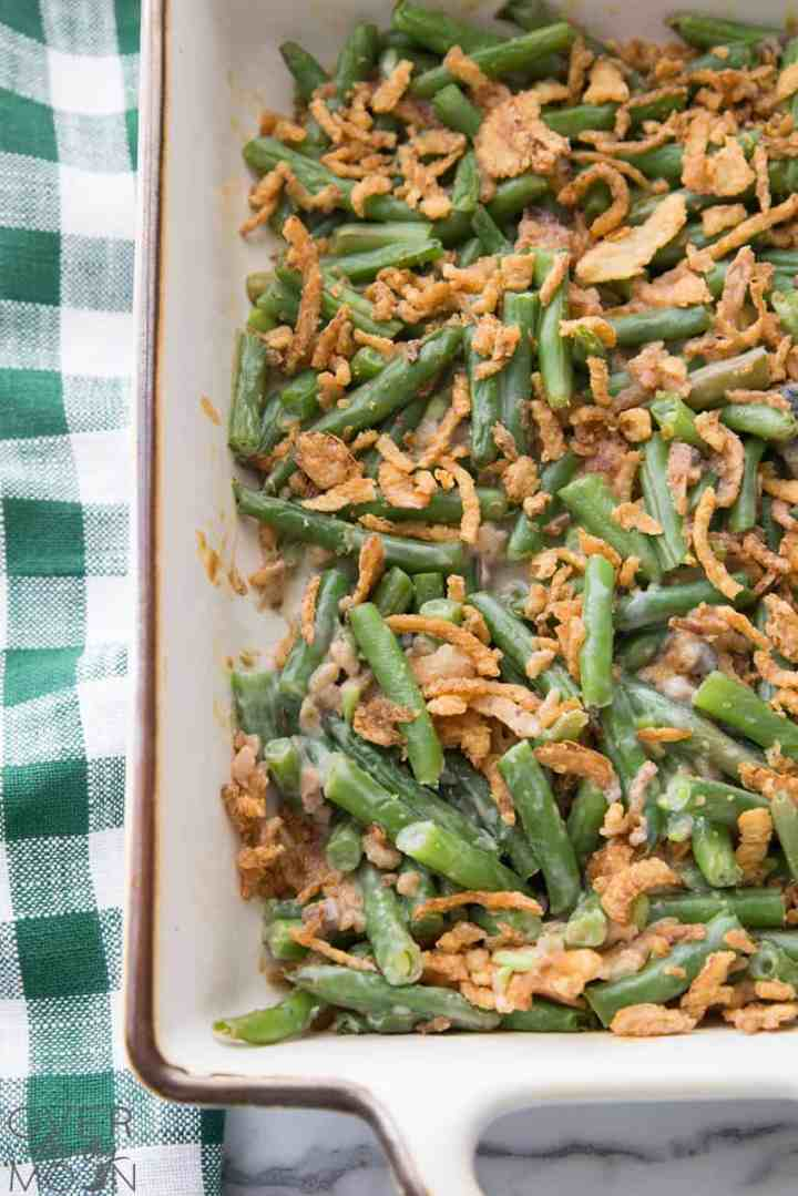 A casserole dish filled with Green Bean Casserole -- green beans in a sauce, topped with french fried onion.