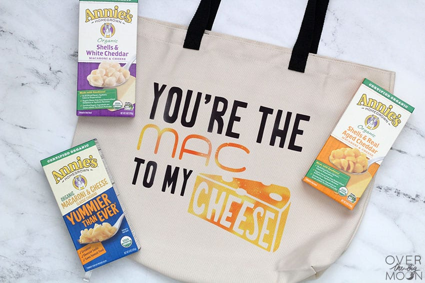 "Tote Bag made using a Cricut machine and Infusible Ink that says ""You're the MAC to my CHEESE!"" There are 3 boxes of Mac N Cheese laying around the bag."