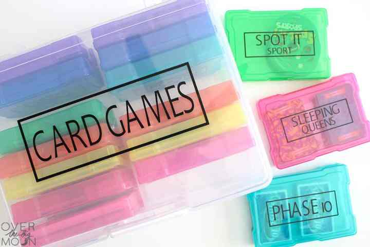 A box large bin filled with small containers that have been made into card game holders. Each container is a different color and has been labeled with the name of the card game.
