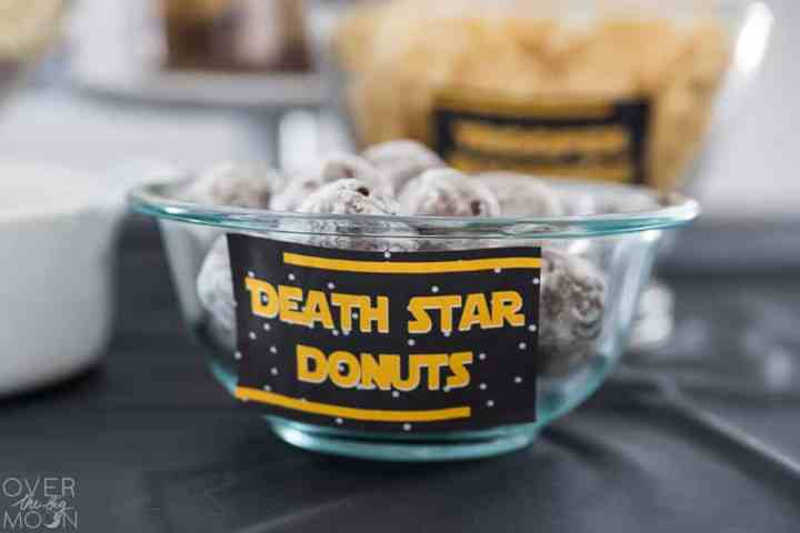 "A bowl full of donut holes with a label that says, ""Death Star Donuts"" on it."