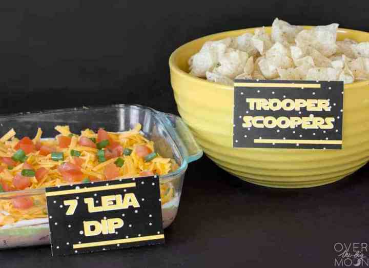 "Star Wars party table with a 7 Layer Dip with a tag that says, ""7 Leia Dip"" and a bowl of tortilla chips that has a tag that says, ""Trooper Scoopers"""