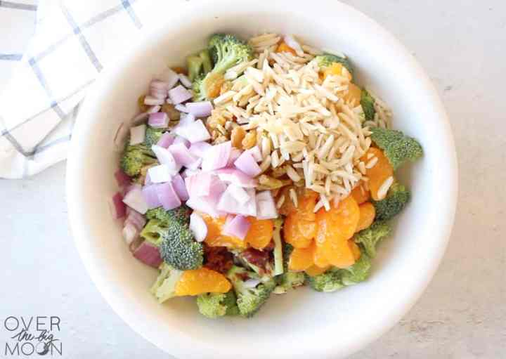 A bowl of broccoli florets, mandarin oranges, chopped red onions, slivered almonds and golden raisins.