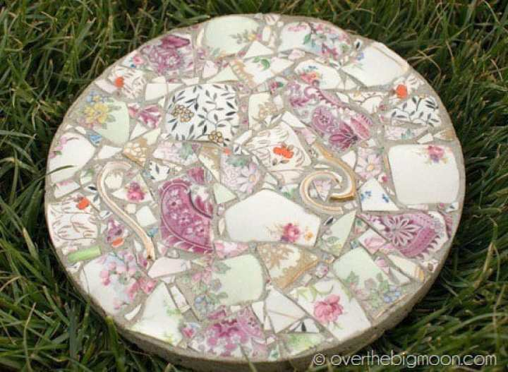 A garden stepping stone made using mortar plaster and broken china pieces.