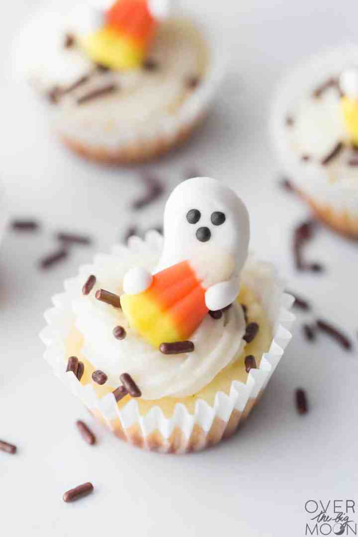 Mini Cheesecake decorated with a marshmallow ghost, candy corn and brown sprinkles.