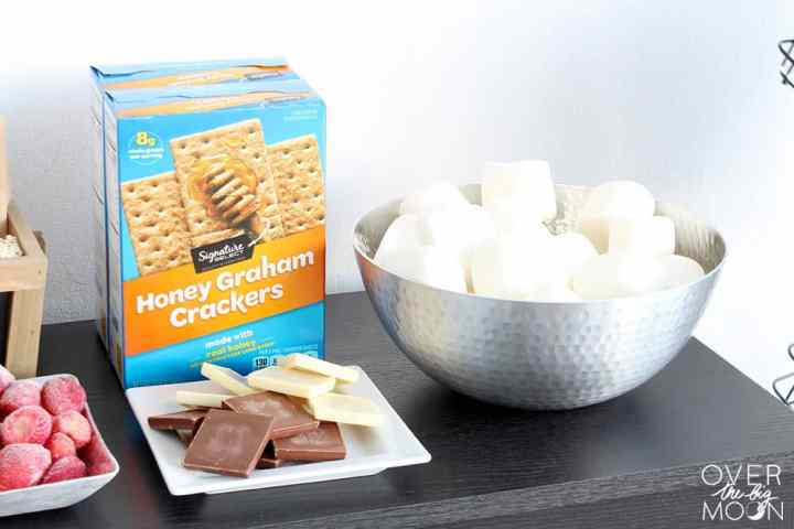 S'Mores ingredients -- box of graham crackeres, plate of chocolate squares and a bowl of large marshmallows.