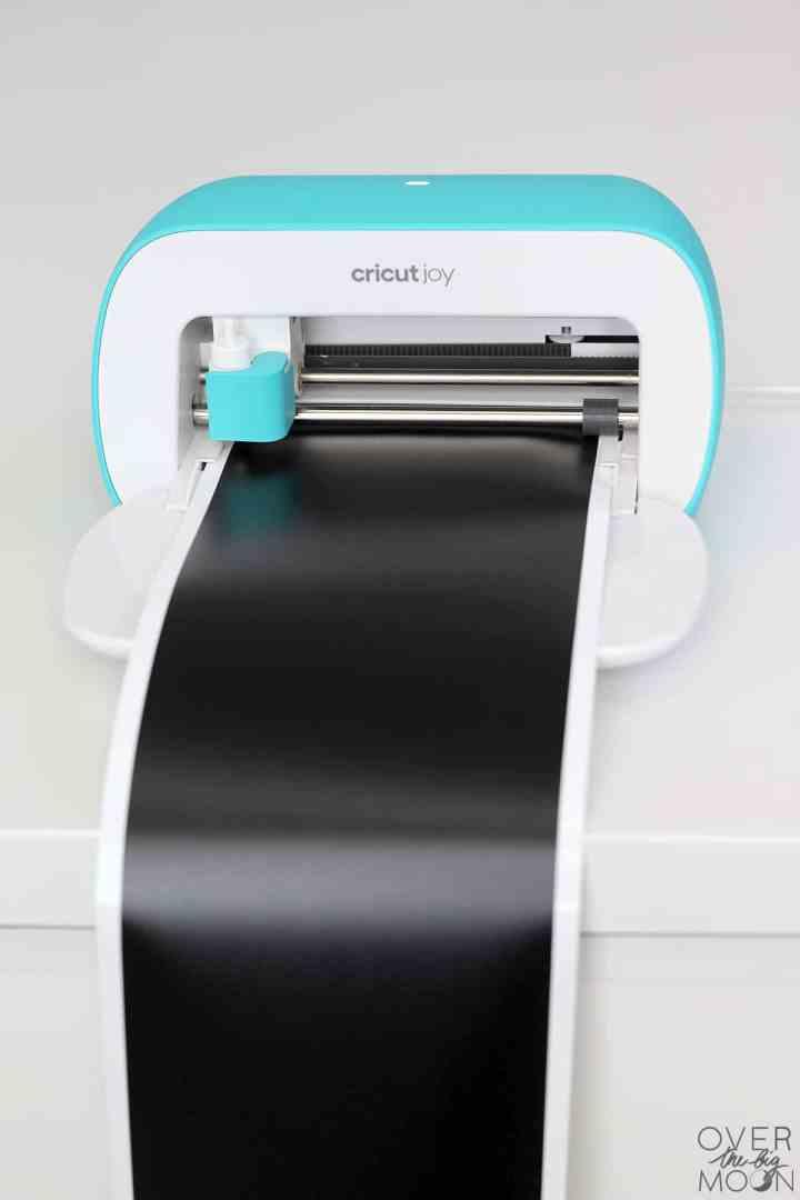 The Cricut Joy machine with Cricut Smart Vinyl loaded in the machine.