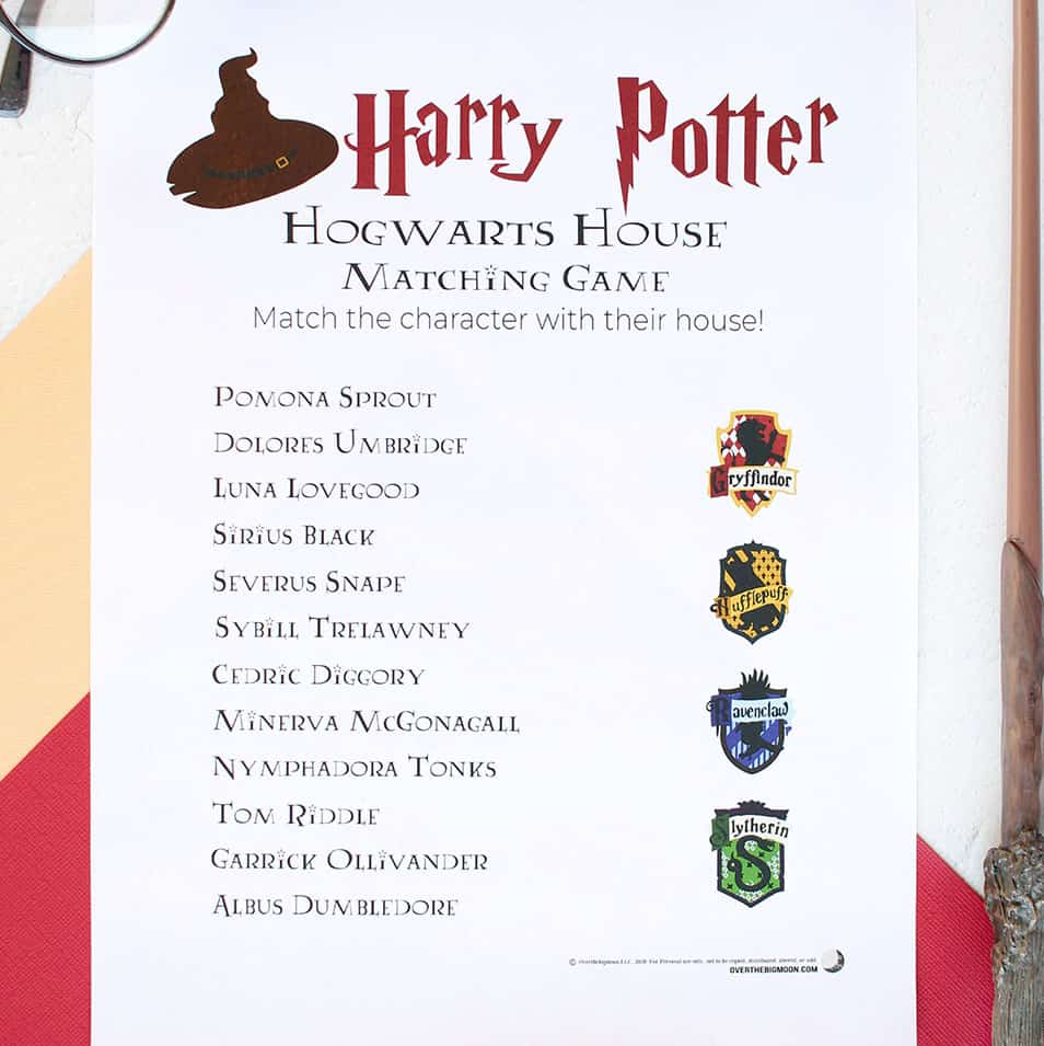 A Harry Potter House Matching Printable Game on a table with Harry Potter Glasses and a wand next to the game.
