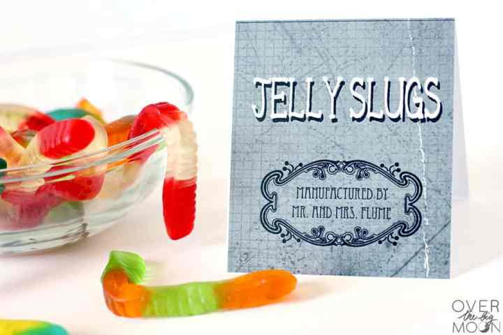 Gummy worms in a clear bowl and on a table with a candy label next to them that says Jelly Slugs.