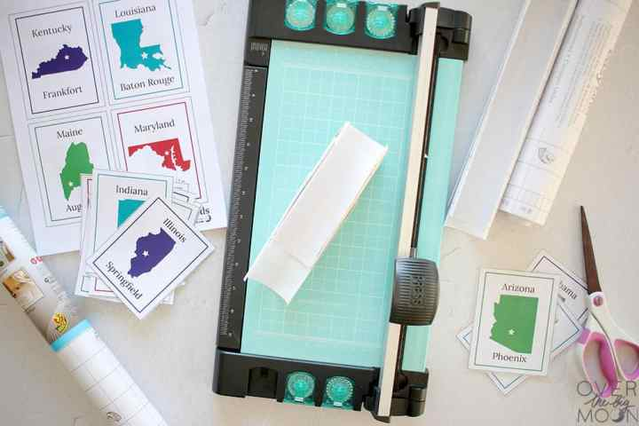 A paper cutter cutting the clear laminate into appropriate sized pieces.