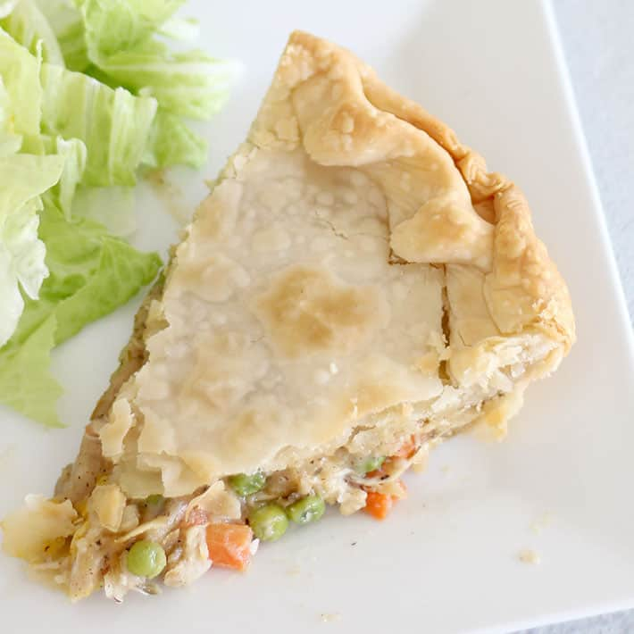An upclose picture of a slice of cooked Homemade Chicken Pot Pie filled with a gravy, peas, carrots and chicken. It is on a white plate with a side green salad.