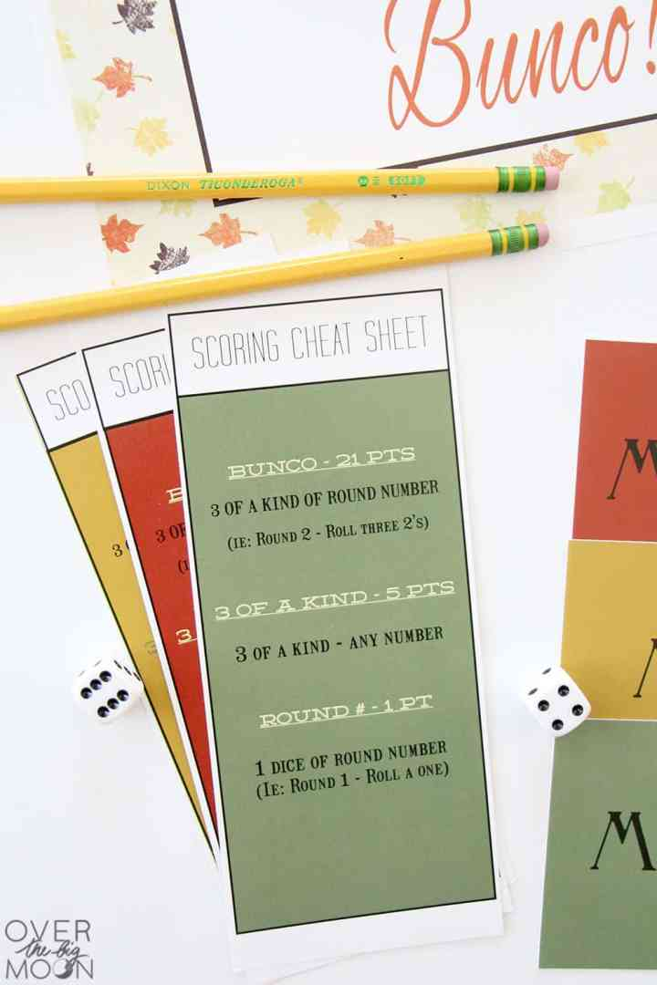 Bunco cheat sheets in green, red and yellow with 2 pencils sitting above them.