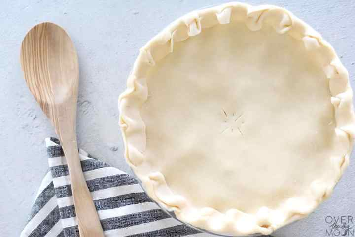 An assembled Homemade Chicken Pot Pie ready to cook. To the left is a wooden spoon.