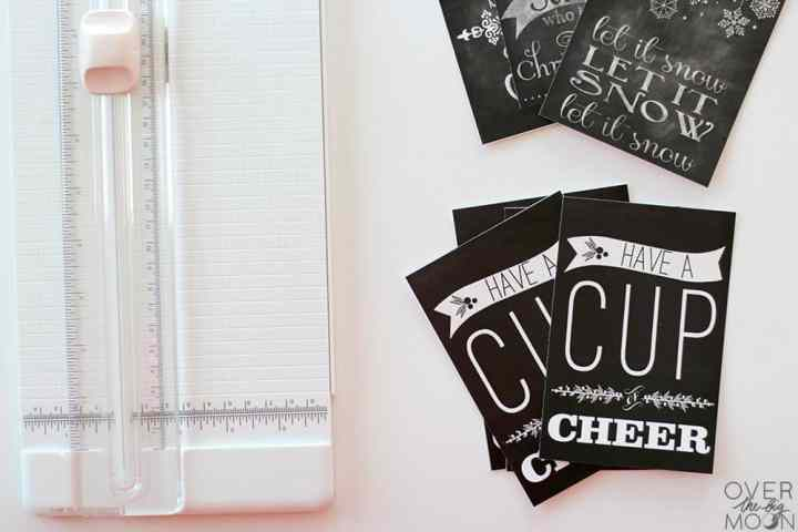 Printed chalkboard printables, cut and sitting next to a paper cutter.