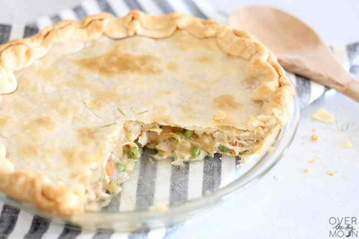 A glass circle pie pan filled with a cooked Chicken Pot Pie in it with a large slice missing. Next to it is a wooden spoon.