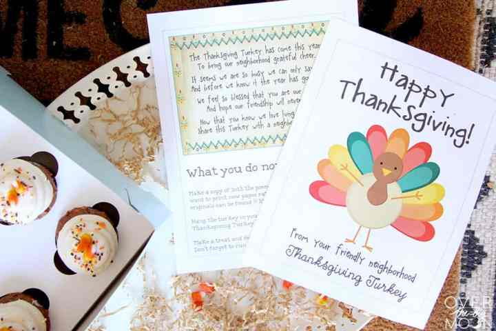 A box of cupcakes next to two printed pages, one with a big turkey on it.