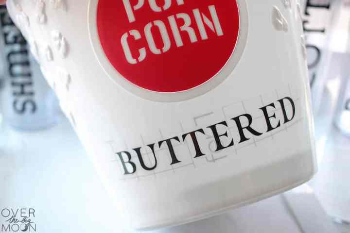 A close up pictures of a Popcorn Bucket with the word Buttered being applied.