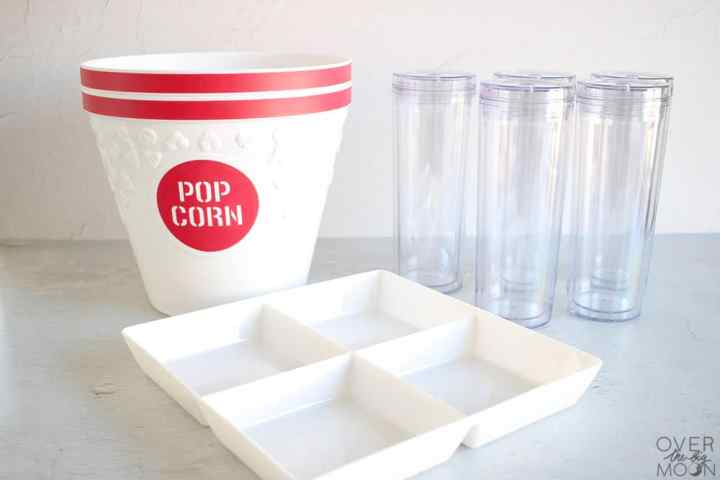2 popcorn buckets, a white serving tray and clear tumblers with straws.