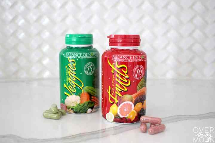 Two pill bottles on a countertop. One bottle is green and labeled Veggies and one is red and labeled fruits. In front of each bottle is a few of the capsules from the bottles.