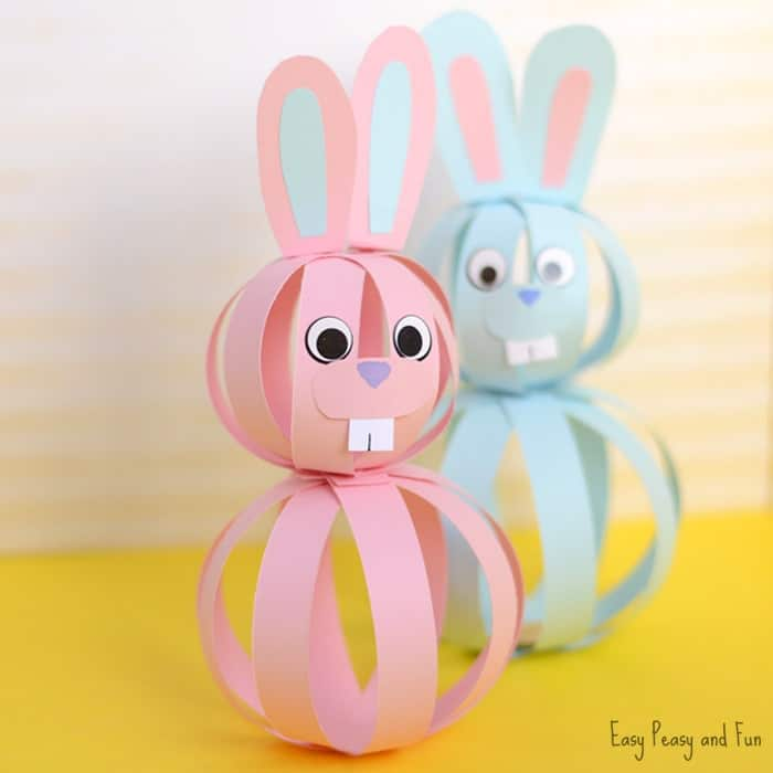 Two bunnies crafted out of paper strips. They strips great two balls that are stacked onto each other. Then there have been paper ears added and some eyes, nose and teeth.