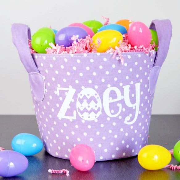 A fabric purple easter basket that has polka dots on it, with the name Zoey in white.