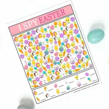 Printable Easter I Spy Game printed and laying on a white surface with colored Easter Eggs all around it.
