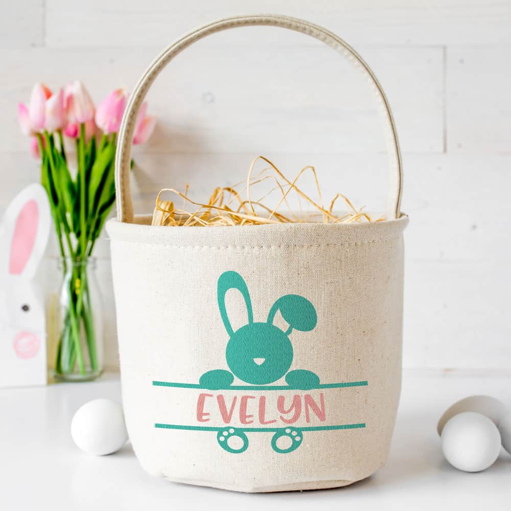 A tan cloth Easter basket personalized with a a turquoise rabbit on the front with the name Evelyn across the center of the bunny. Behind the basket are some pink tulips.