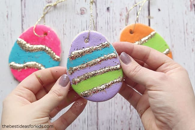 Easter eggs made from Salt Dough and painted purple, blue, green, orange and pink. Gold Glitter glue is added in stripes.