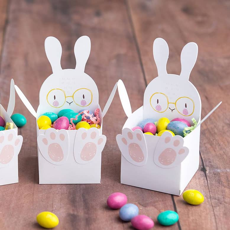 Paper cups shaped like a bunny filled with Easter candy.