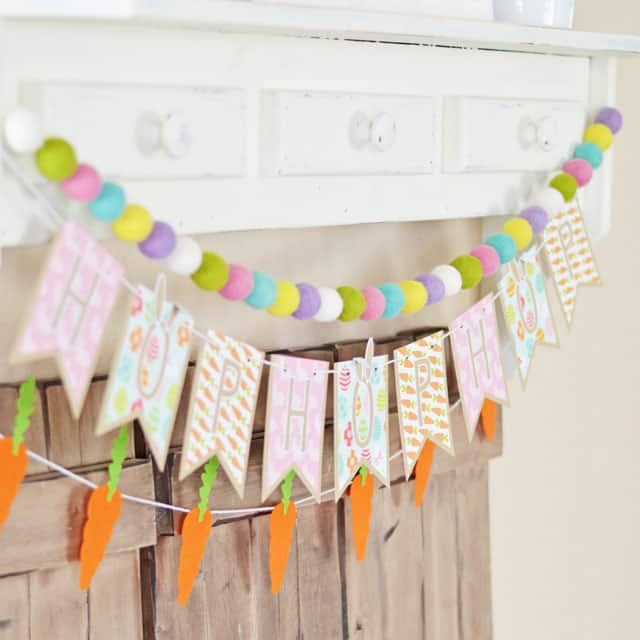 An Easter bunting, with a carrot bunting below it and a pom pom bunting above it hanging from a shelf.