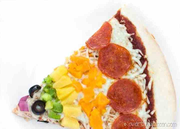 A piece of a rainbow pizza cut showing all the amazing colors