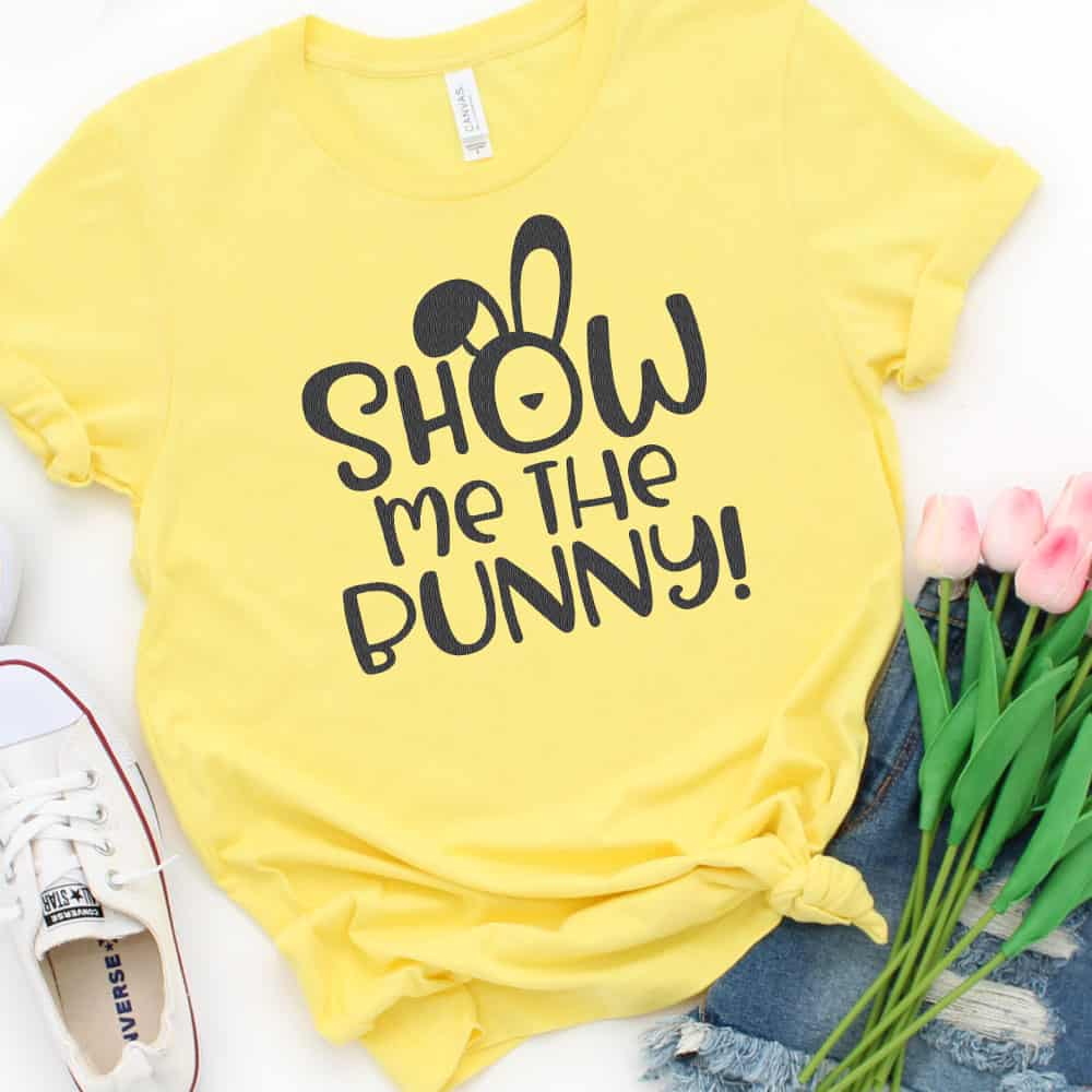 """A yellow shirt with the design """"Show Me the Bunny!"""" with pink tulips to the right of the shirt and white converse to the left side of the shirt."""