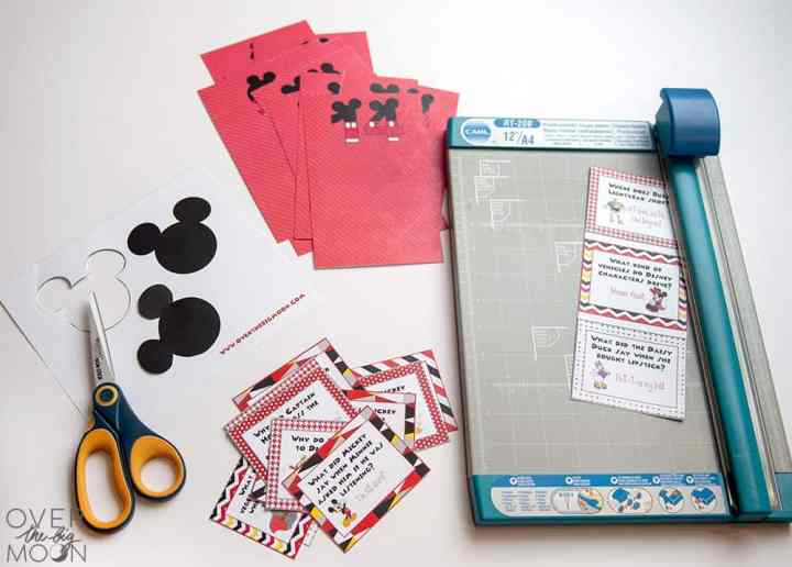 Cut up printed Disney Joke Cards and Red envelopes next to a paper trimmer.