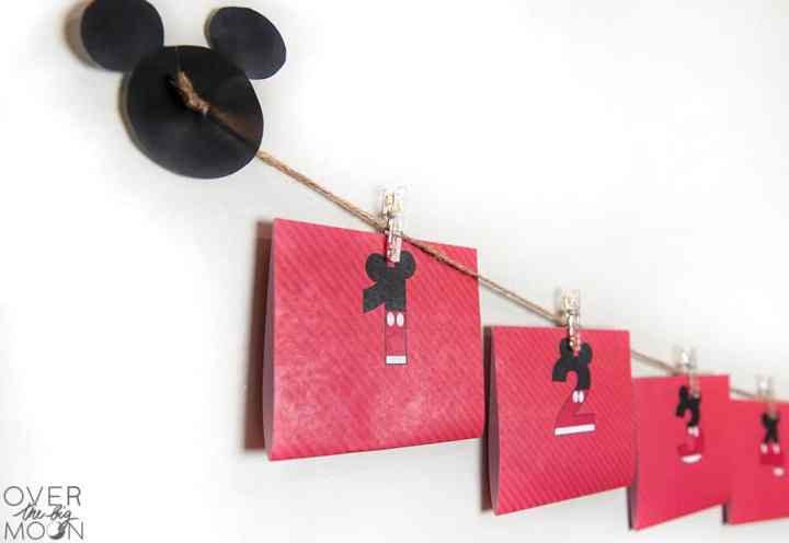 A disney countdown created using printables, twine and clips hanging on the wall.