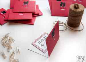 A joke card being placed inside the Disney Countdown card. To the side is a roll of twine and to the other side is a pile of binder clips.