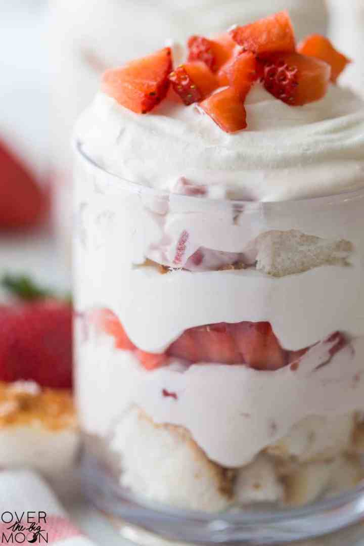 A clear class with a layered strawberry and cream cheese trifle in it. You can see cut up strawberries, cubed shortcake and coolwhip.