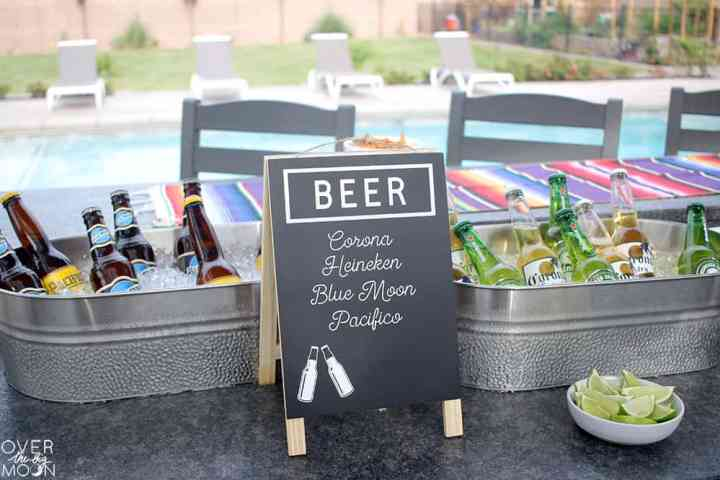 A sign that says Beer and lists Corona, Heineken, Blue Moon and Pacifico on it. Then there's two tubs of bottled beer.