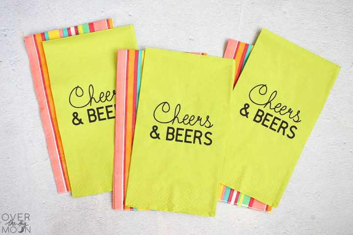 A pile of napkins that are lime green and say Cheers and Beers on them. Under the lime green napkins are colorful napkins.