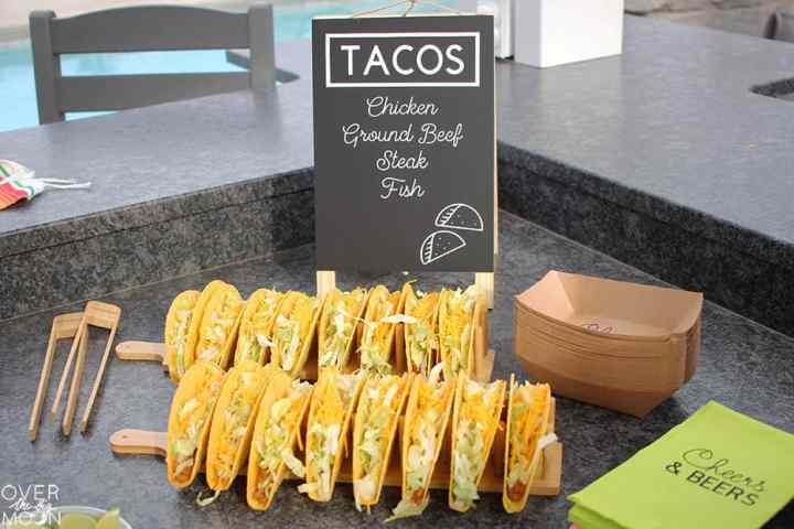 Tacos displayed on a wooden rack with a Taco menu sign in the background.