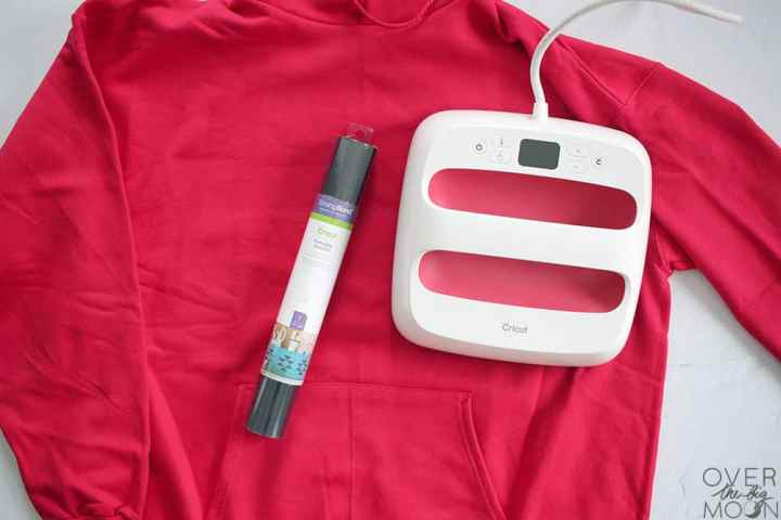 A red hoodie with the EasyPress 2 laying on top of it and a roll of black Iron On.