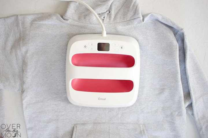 A gray hoodie with the EasyPress 2 in the center of the chest transferring an Iron On design.