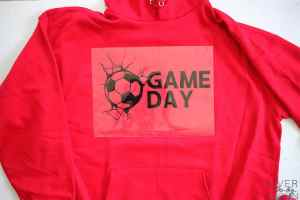 An Iron On Design that says Game Day with a soccer ball on a red hoodie.