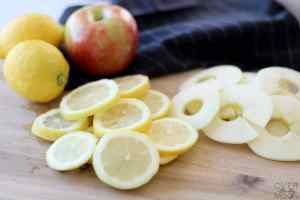 A cutting board with apple slices and lemon slices on it.