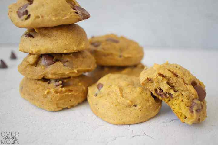 8 pumpkin chocolate chip cookies stacked on a white counter. The cookie in the front has a bite out of it.