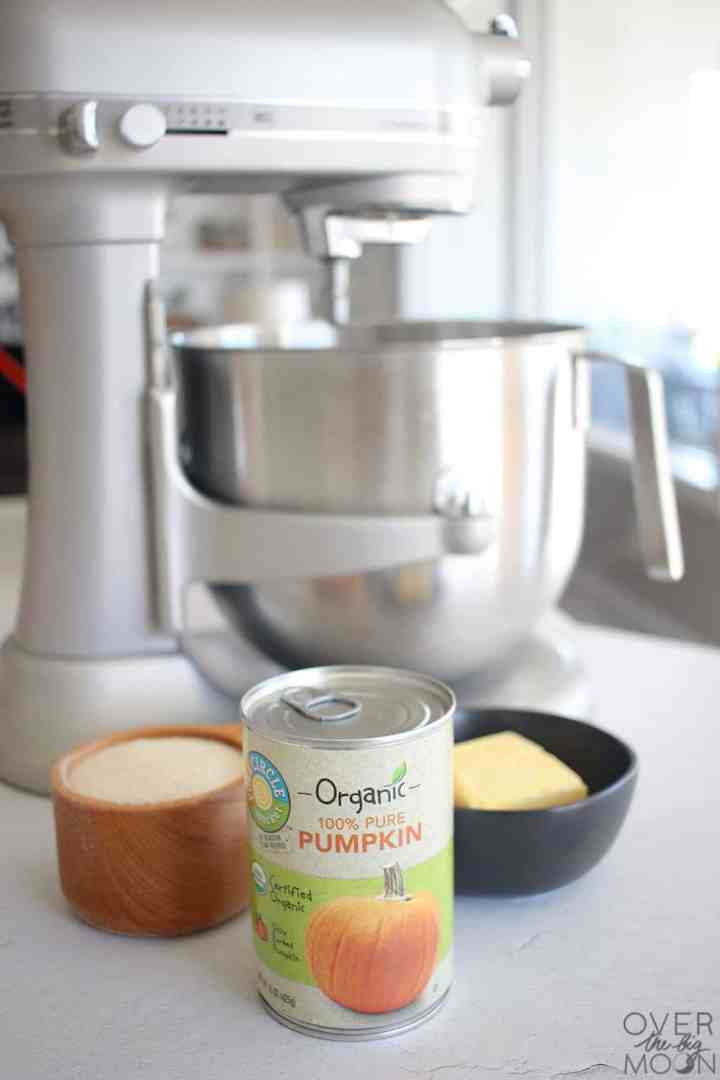 A silver kitchen aid with a cup of sugar, can of pumpkin and a bowl of butter.